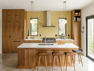 For the backsplash, the homeowner chose ceramic tiles in a honeycomb pattern by Portland-based Clayhaus to compliment the walnut-faced cabinetry.
