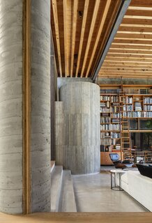 Throughout the house, a few recurring themes emerge: glass walls, steel framing, floor-to-ceiling bookcases, and rolling library ladders. The interiors are furnished with midcentury classics, including a vintage Eames Lounge chair, alongside Japanese works of art.