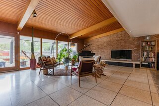 Expansive glass doors extend the living room to the gathering area in the backyard. The wood-clad ceiling and exposed beams are original to the home.