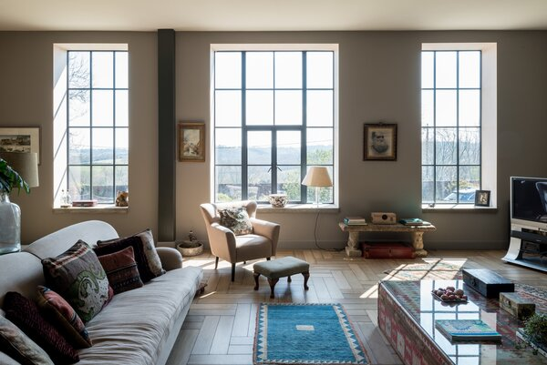 Black-trimmed windows line the exterior, capturing the home's uninterrupted countryside views.