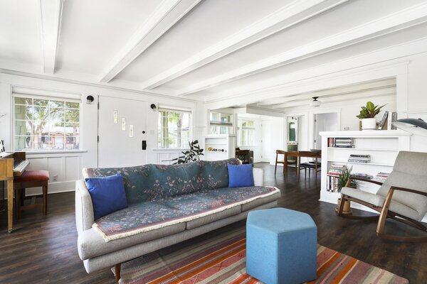 Another view of the primary living area showcasing the home's free-flowing layout, as well as the original wainscoting and casement windows sandwiching the main entrance.