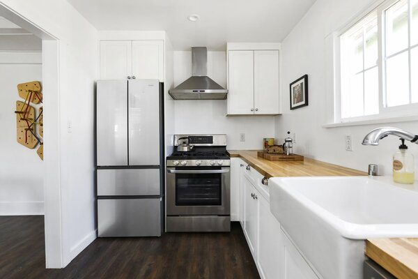 Nestled behind the dining area, the kitchen includes a large farmhouse sink and laundry cabinet.