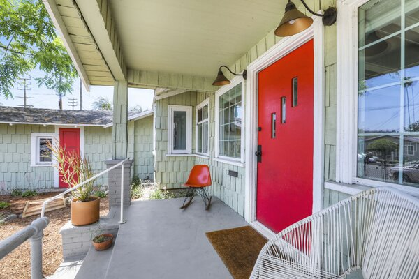 The residence draws instant curb appeal with its vibrant red front door. The warm welcome is extended by the covered porch overlooking the lawn—an idyllic setting to sip morning coffee.