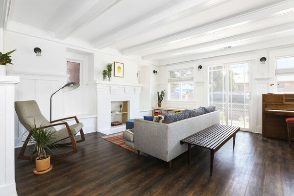 Refinished hardwoods line the floors, contrasting with the surrounding white walls and ceilings.