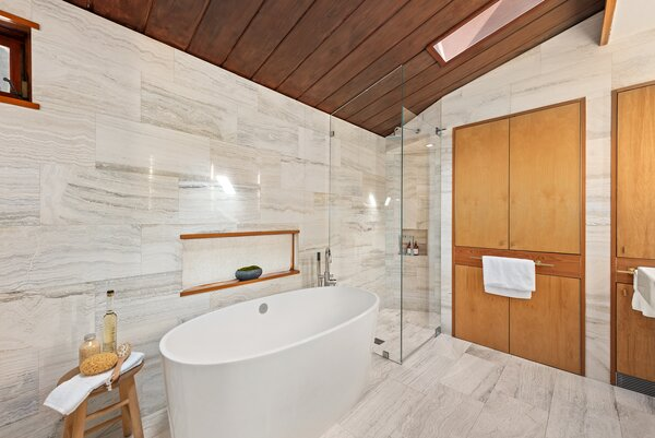 Included in the primary suite is a large spa-like bath, complete with travertine walls, heated floors, and an oversized freestanding tub.