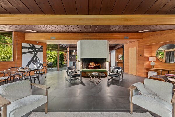 The broad concrete fireplace serves as a subtle partition between the living room and kitchen.