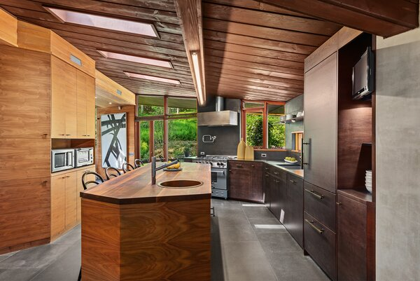 A central wooden island provides additional counter space, as well as bar-stool seating.