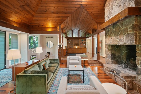 In the living room, recessed lighting is used to emphasize the original wood-clad ceilings.