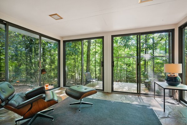 Sliding glass doors wrap around the rear sunroom, opening the space to the wooded lot.