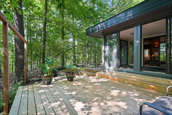 The sunroom is extended outdoors via a generous deck, offering a shaded corner to relax.