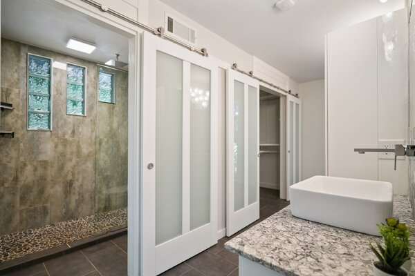 In the bathroom, two sets of sliding doors unveil an oversized shower and a walk-in closet.