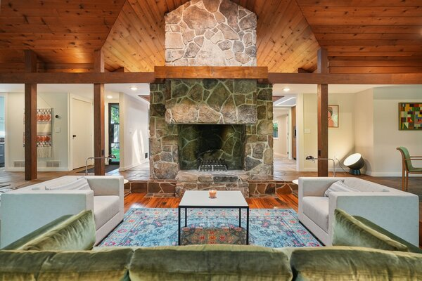 The broad stone fireplace soars to the ceiling, enhancing the room's overall sense of space.