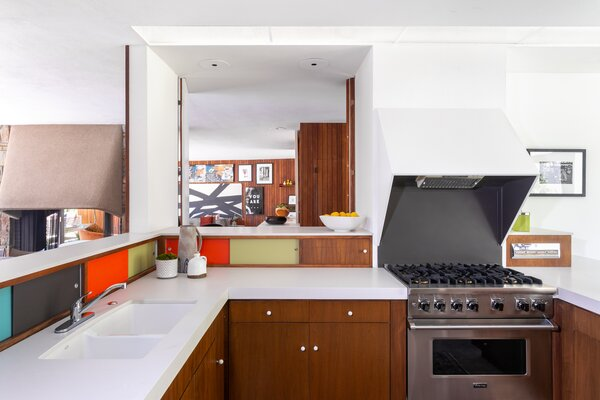 Another view of the kitchen showcasing the original sliding cabinets, which now add playful pops of color to the space.