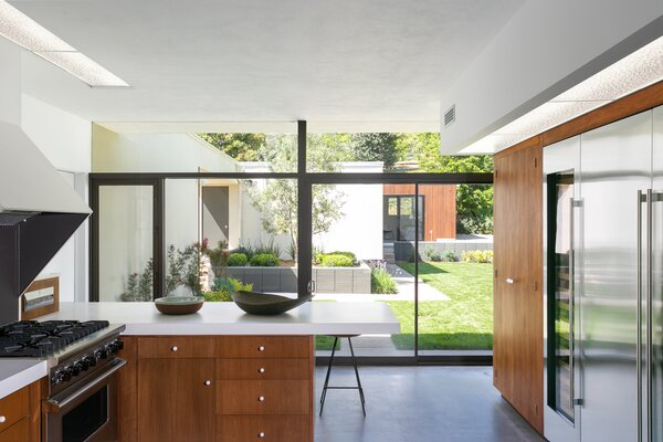 The kitchen—fitted with restored mahogany cabinetry and Formica countertops—overlooks the landscaped yard.