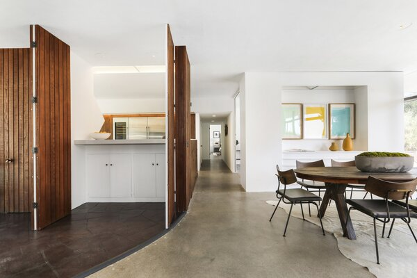 Floor-to-ceiling doors open up the central kitchen to the primary living spaces.
