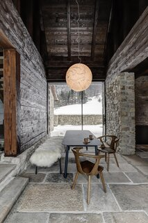 The dining area is located in what used to be the passageway between the house and the barn. A Moon luminaire by designer Davide Groppi hangs above the table, with tall, sliding glass doors extending the space to the enclosed yard.