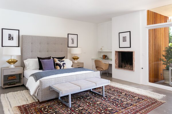 The primary suite is located down the hall from the main living spaces and features another fireplace, as well as direct access to the backyard pool.