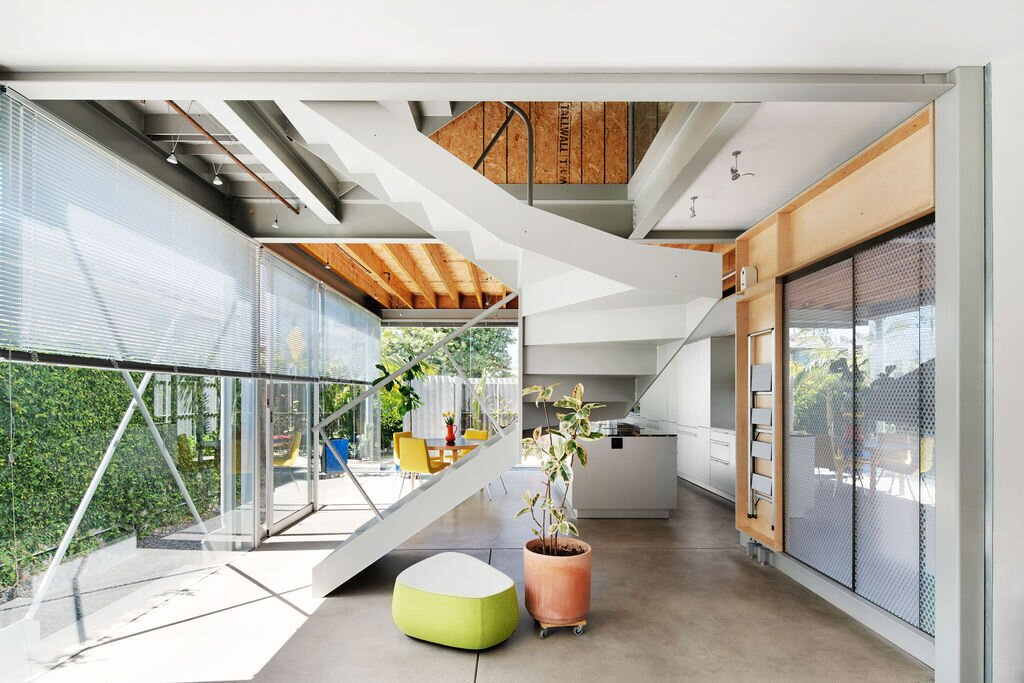 The couple designed the three-floor residence around the central spiral staircase. Expansive walls of glass wrap around the ground-level living spaces, opening the home up to the outdoors.  Photo 3 of 14 in Listed for $2.7M, This Architect's Award-Winning Home in Southern California Is a Must-See