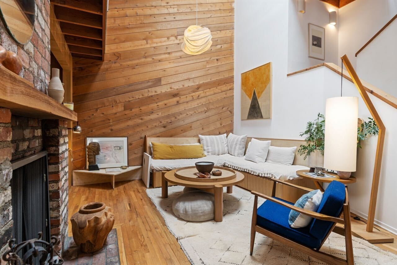 Wood-clad walls continue into the primary living room, complete with tall ceilings and an original red-brick fireplace. The home's central staircase sits to the right.  Photo 3 of 14 in A Tree House–Like Dwelling Near the Coastline Seeks $3.89M in Santa Monica, CA
