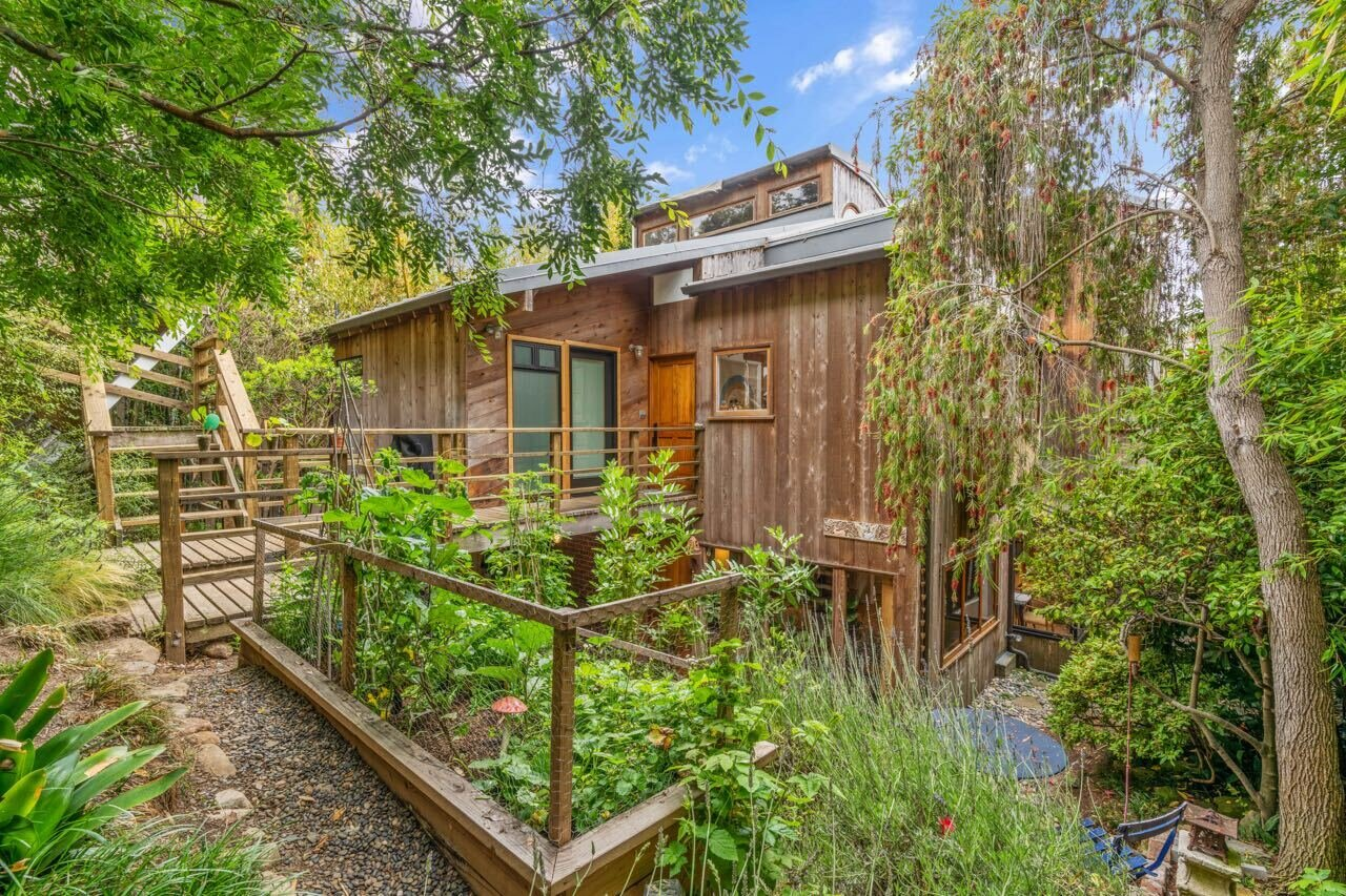 Though conveniently located in Santa Monica, the 1981 home feels worlds apart as a result of its nestled positioning among mature vegetation. Thriving raised-bed gardens lining the walkway helps transform the property into the serene, grounded environment Roberts initially envisioned.  Photo 1 of 14 in A Tree House–Like Dwelling Near the Coastline Seeks $3.89M in Santa Monica, CA
