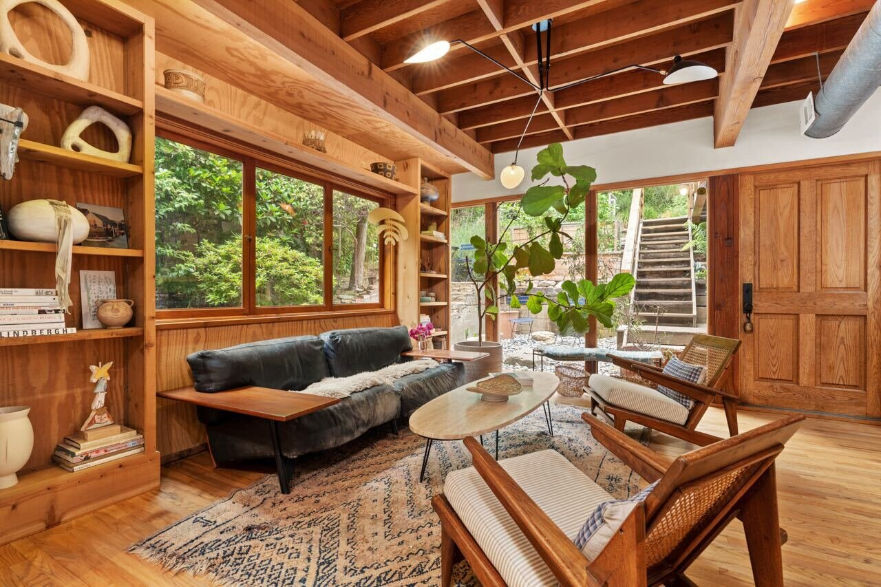 Upon entry is a sun-kissed living area featuring wood-clad walls with custom built-in shelving.  Photo 2 of 14 in A Tree House–Like Dwelling Near the Coastline Seeks $3.89M in Santa Monica, CA