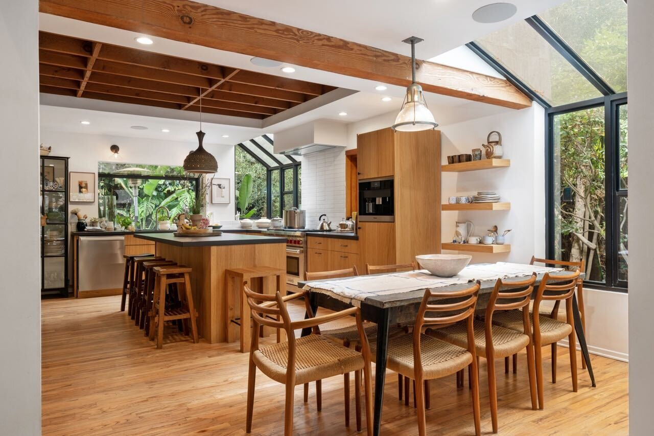 An exposed wooden beam serves as a subtle divider between the open dining area and kitchen.  Photo 5 of 14 in A Tree House–Like Dwelling Near the Coastline Seeks $3.89M in Santa Monica, CA