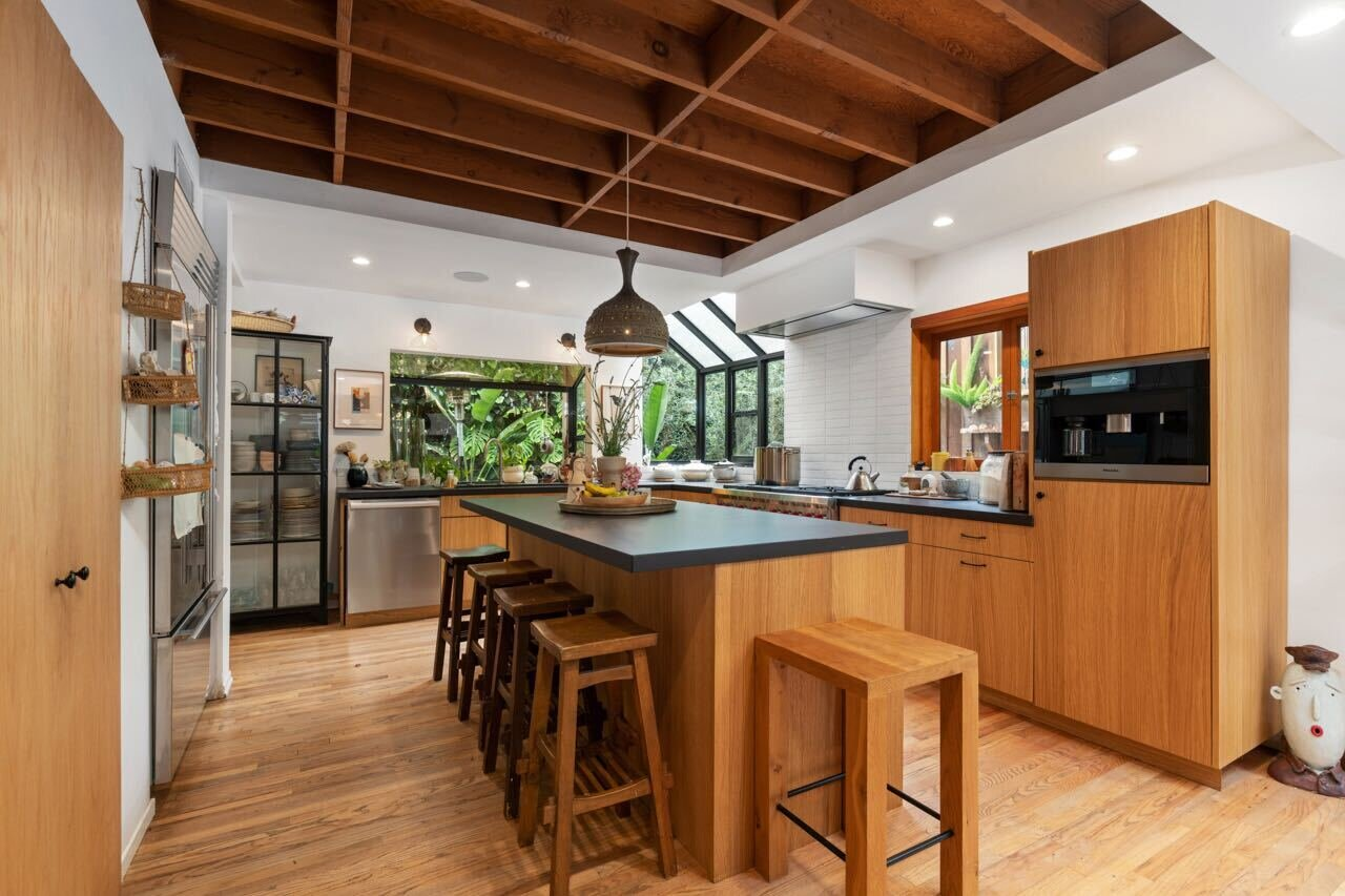Greenhouse–inspired glazing invites additional light inside the corner kitchen, which is anchored by a large wooden island and fitted with top-of-the-line appliances.  Photo 6 of 14 in A Tree House–Like Dwelling Near the Coastline Seeks $3.89M in Santa Monica, CA