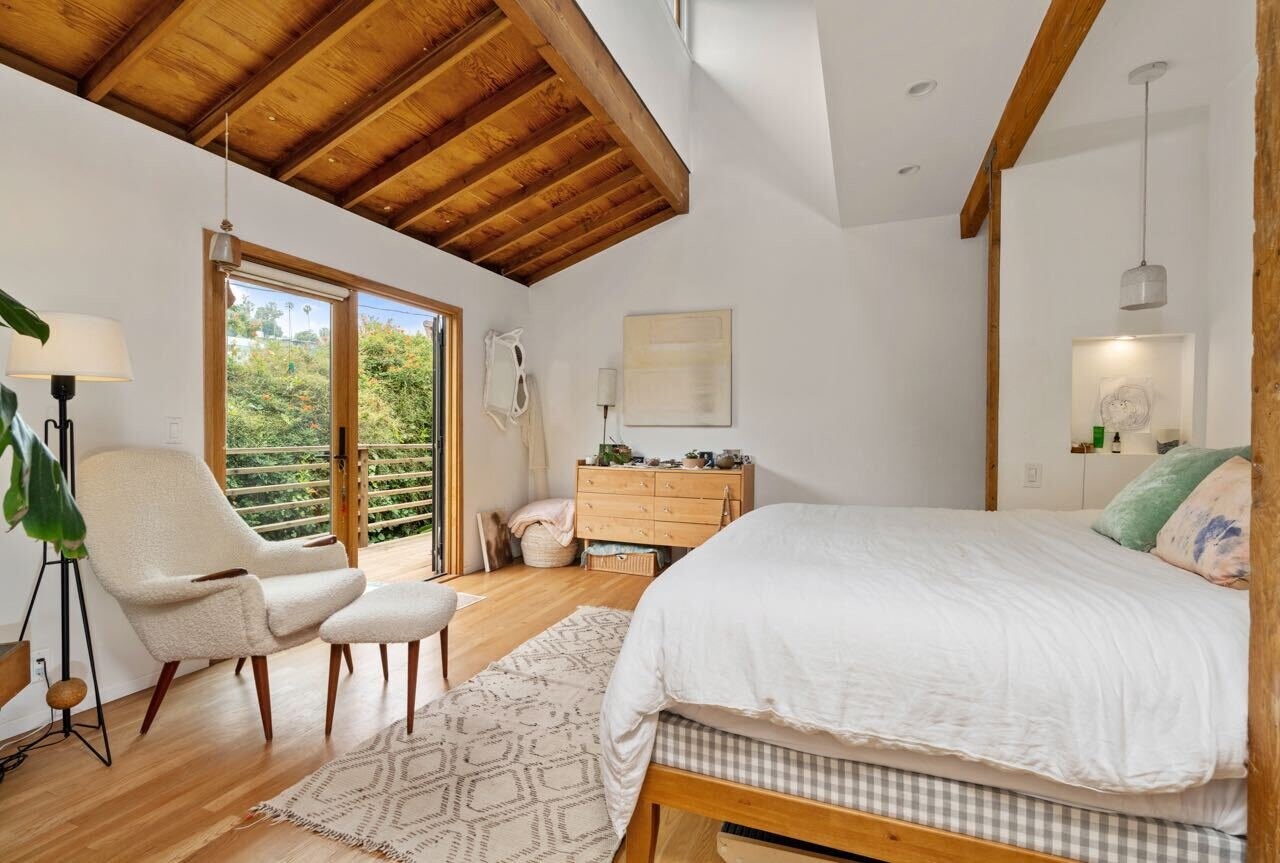 In total, the property includes five bedrooms—four of which are inside the main residence and an additional guest suite located outside. Here is a look at the primary bedroom suite, which comes with a private terrace.  Photo 8 of 14 in A Tree House–Like Dwelling Near the Coastline Seeks $3.89M in Santa Monica, CA