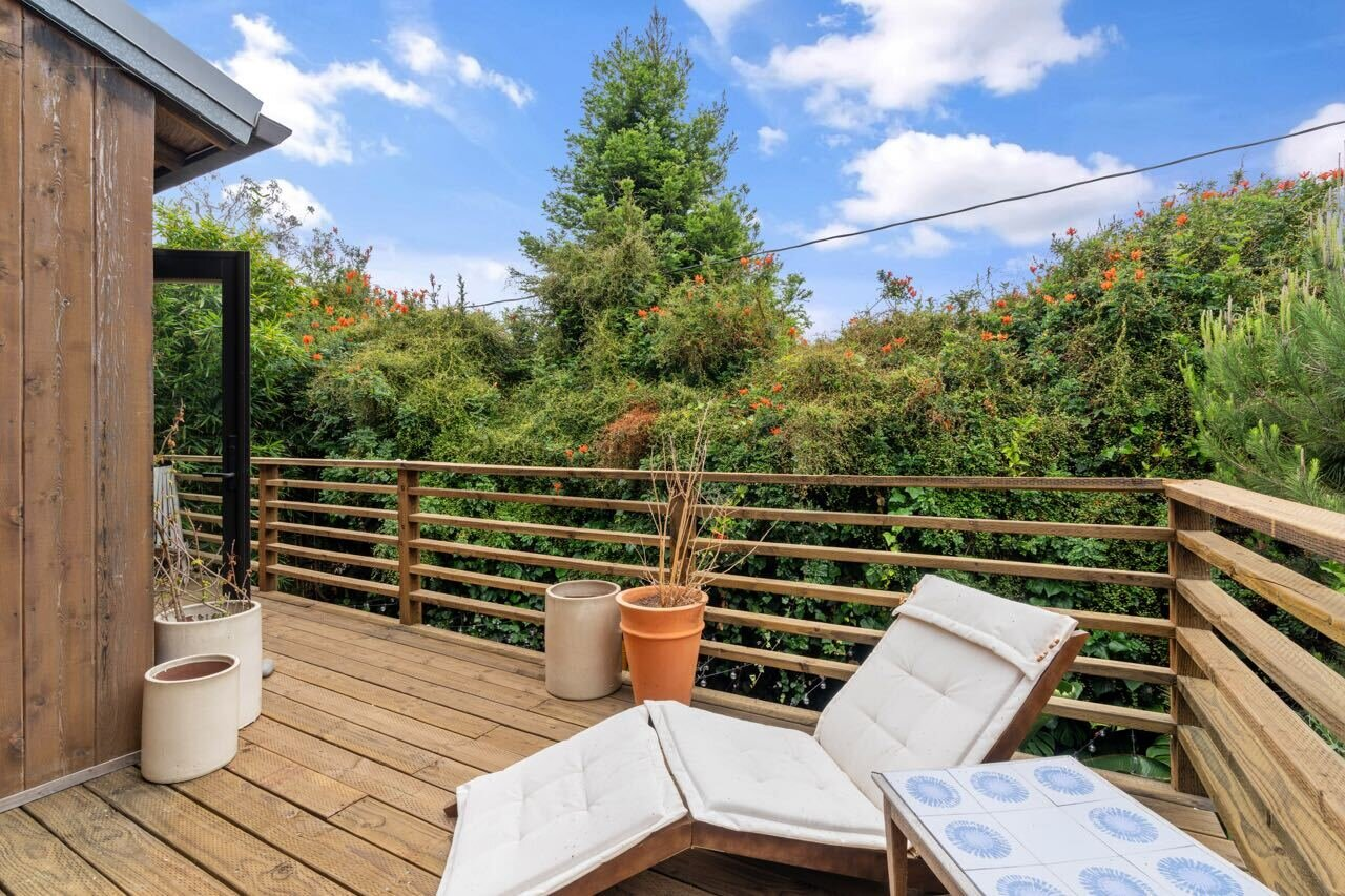 The adjacent terrace is surrounded by mature trees, ensuring ample privacy.  Photo 10 of 14 in A Tree House–Like Dwelling Near the Coastline Seeks $3.89M in Santa Monica, CA