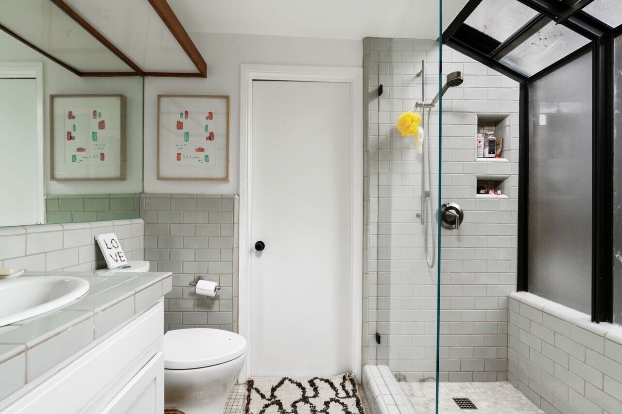 Another one of the four baths is dressed with light-gray tiles and boasts a large glass shower.  Photo 13 of 14 in A Tree House–Like Dwelling Near the Coastline Seeks $3.89M in Santa Monica, CA