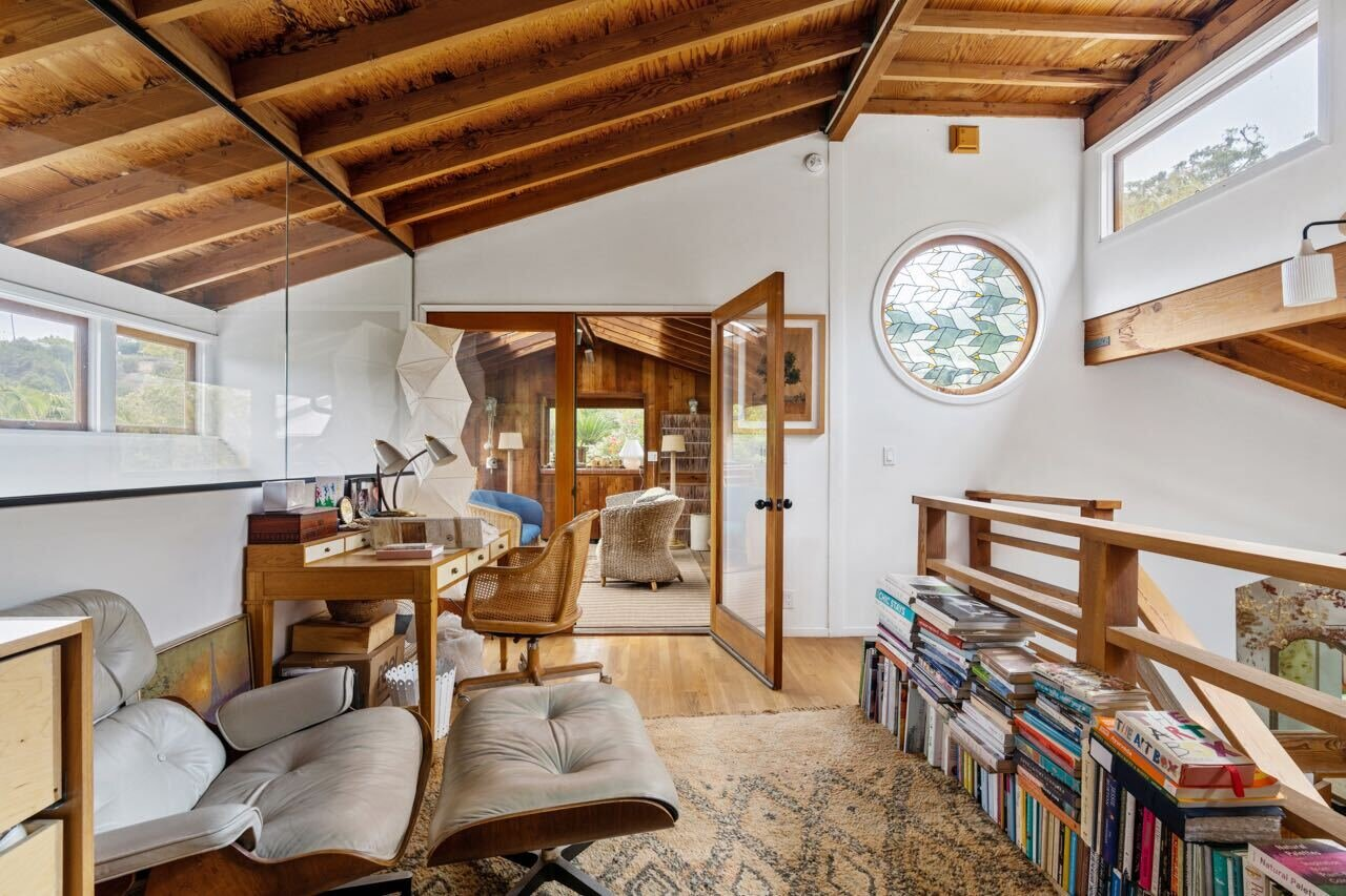 A cozy study area awaits at the base of the top floor. A circular stained-glass window infuses the tree house-like space with whimsical flair.  Photo 11 of 14 in A Tree House–Like Dwelling Near the Coastline Seeks $3.89M in Santa Monica, CA
