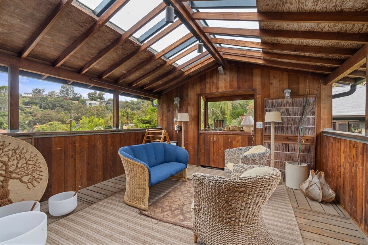Right off the study area is an open creative studio. Wrapped and capped with wood and windows, the illuminated space can also serve as an additional bedroom or home office.  Photo 12 of 14 in A Tree House–Like Dwelling Near the Coastline Seeks $3.89M in Santa Monica, CA