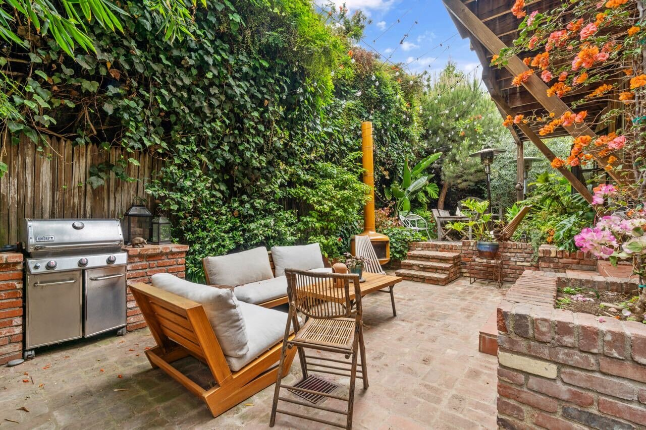 Once the sun sets, Edison lights illuminate the spacious brick patio in the backyard, presenting a charming corner for memorable entertaining.  Photo 14 of 14 in A Tree House–Like Dwelling Near the Coastline Seeks $3.89M in Santa Monica, CA