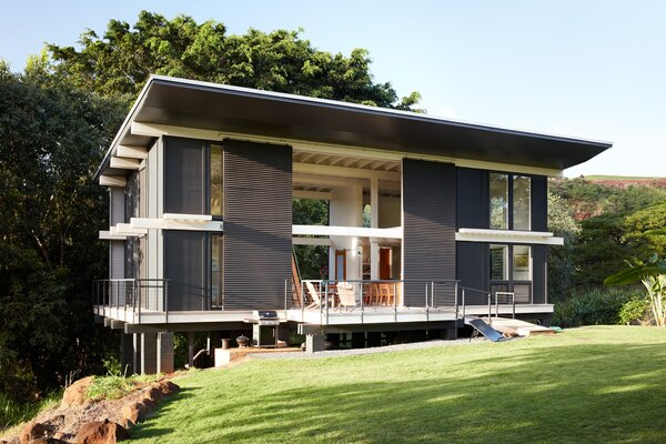 At James and Sara Davis's weekend home on O'ahu, double-height doors open to a lanai-like space at the center of the house. The home's energy needs are met via solar panels set by the entry.