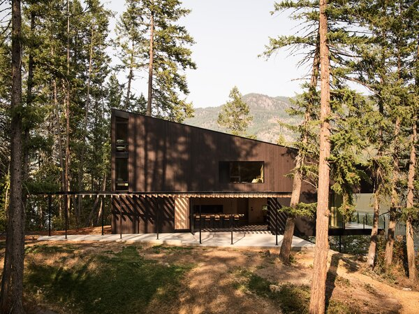 The cabin's exterior is clad in dark-stained western red cedar and fiber cement panels, and its cantilevered deck provides panoramic views.