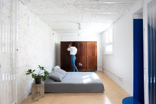 Upstairs, the primary bedroom is spartan, with just a bed and an antique wardrobe. The former studio's rough walls and ceiling were left uncovered and painted white.