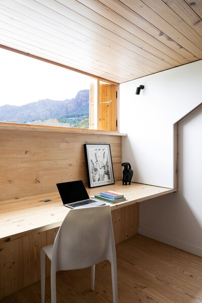 """In the study on the home's top level, a long window provides a panoramic view of Newlands Forest and Table Mountain. """"The light in the morning is amazing, and the view of the mountain is incredible,"""" Derek says."""