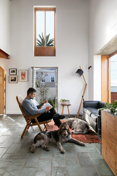 Derek and the dogs bask in the warm sunlight by one of the bay windows. Derek and Jean are keen supporters of local artists, and they have decorated the space with pieces by Banele Khoza, Conrad Botes, and Jeanne Gaigher. The living room lamp is by Douglas's husband and firm partner, Jan, while the bentwood armchair and side tables are vintage finds.