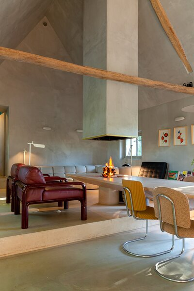 A pink concrete dining-cum-coffee table holds a fire-pit at one end, where it's surrounded by a pair of Gae Aulenti lounge chairs, a Tufty Time sofa from B&B Italia, and a Mies van der Rohe Barcelona chair. The 1930s dining chairs are by Hynek Gottwald.