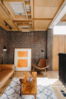 The contemporary wood panelling continues into the top-level lounge space, complementing the surrounding brick walls and oak hardwood flooring.
