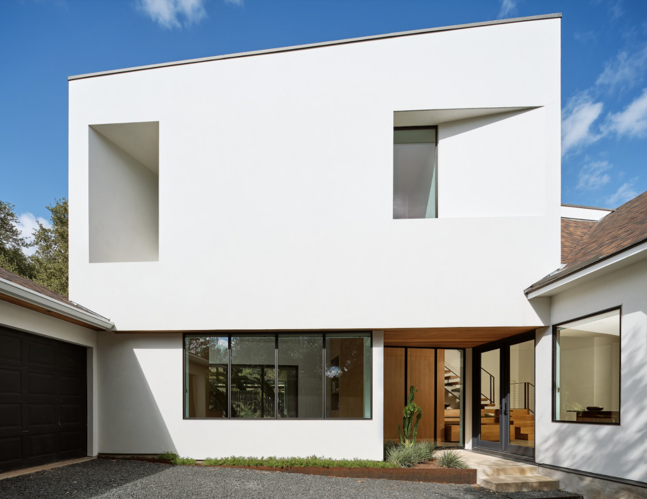 The aim of this project was to connect the existing house and garage with a distinctly contemporary addition.  Photo 2 of 9 in This Striking Addition in Austin Is Defined by Clean, Discrete Geometry from Ames House by Matt Fajkus Architecture