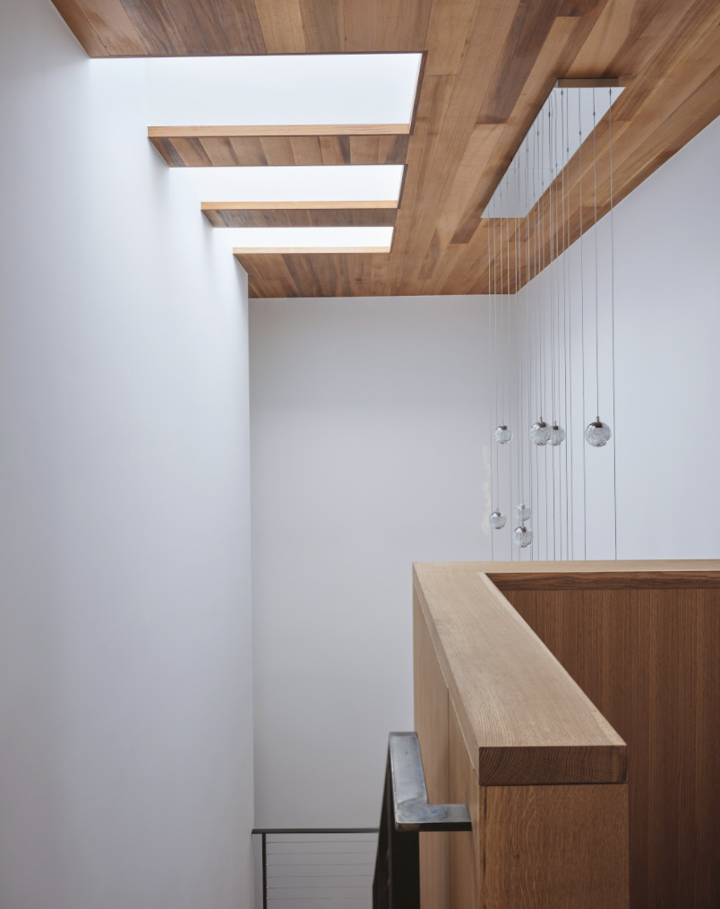 A custom light fixture adorns the new stairwell.  Photo 4 of 9 in This Striking Addition in Austin Is Defined by Clean, Discrete Geometry from Ames House by Matt Fajkus Architecture