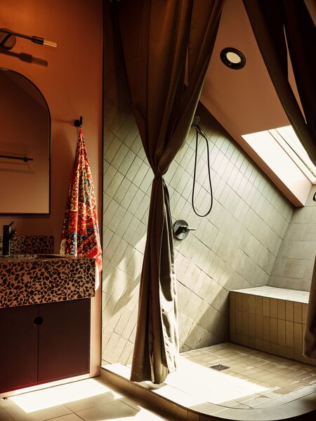 """The upstairs bathroom features a shower nook with a skylight. """"You can look out and see palm trees,"""" Kuo says."""