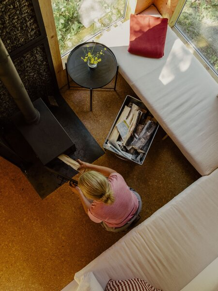 The living area is furnished with a Gladom side table, a throw pillow, and cushions—all from Ikea. At night, the loft ladder leans over the sofa, secured with a bungee cord; during the day, it props up beside the Woodsman fireplace.