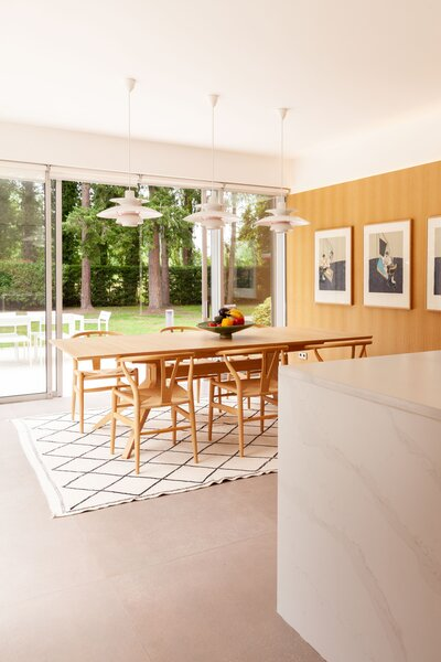 The dining area features a trio of PH5 pendants by Louis Poulsen, a Cross oak table by Matthew Hilton, and Wishbone CH24 chairs by Hans Wegner for Carl Hansen & Søn.