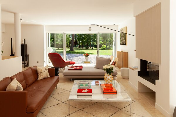In the living room, a Stricto Sensu sofa by Didier Gomez and a Prado daybed by Christian Werner, both from Cinna, join a marble-topped coffee table by Florence Knoll. The red easy chair and ottoman are from the Platner Collection by Knoll, joined by a stool from La Redoute, a Tulip side table by Eero Saarinen for Knoll, and a pair of PK22 chairs by Poul Kjærholm for Fritz Hansen. The black Potence wall lamp is by Jean Prouvé while the tiles on the floor and above the fireplace are from Living Ceramics.
