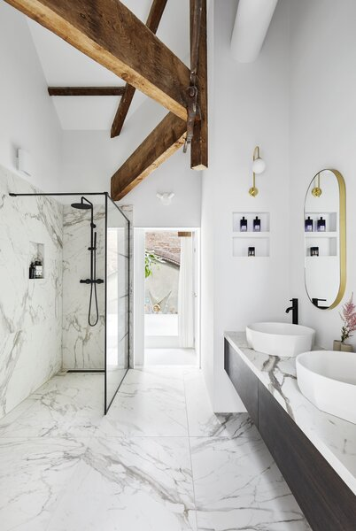 A marble-clad bathroom joins the bedroom and overlooks the skylit living area below.