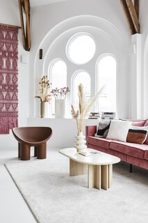 In a raised sitting area surrounded by arched windows, a pink couch by Be Pure Home matches a wall hanging made by Milla.