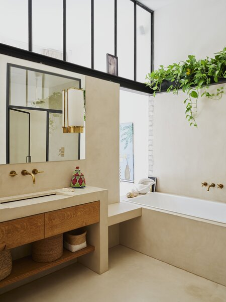 The adjoining bathroom gets indirect daylight via openings in the brick wall and a transom window.