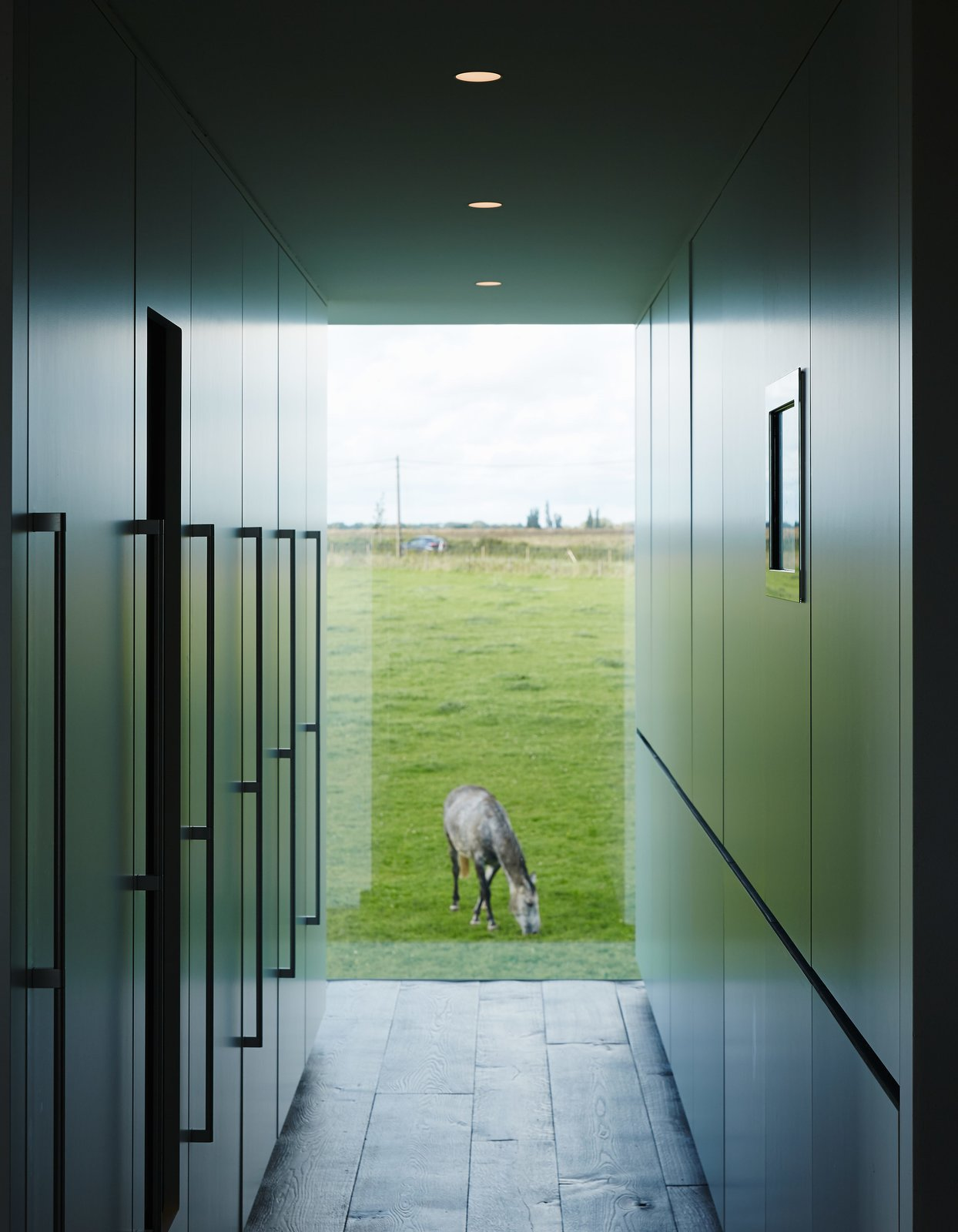Discreet kitchen storage, which conceals the refrigerator, a wine cooler, the freezer, recycling, and cleaning materials, complements a view of one of the family's five horses.  Wynant House